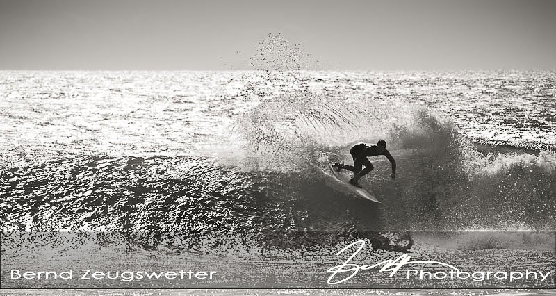 surfer turing on top of the wave