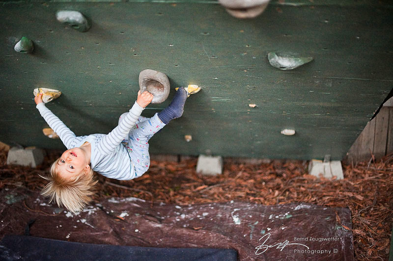 Child monkeying around on climbing wall.