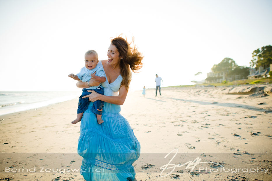 Mother and baby boy jumping for joy on the beach, Montecito, California.