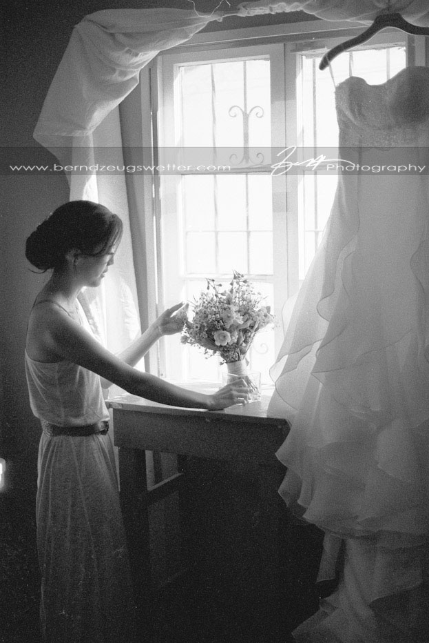 Bride looking at bouquet with wedding dress hanging, Santa Barbara.