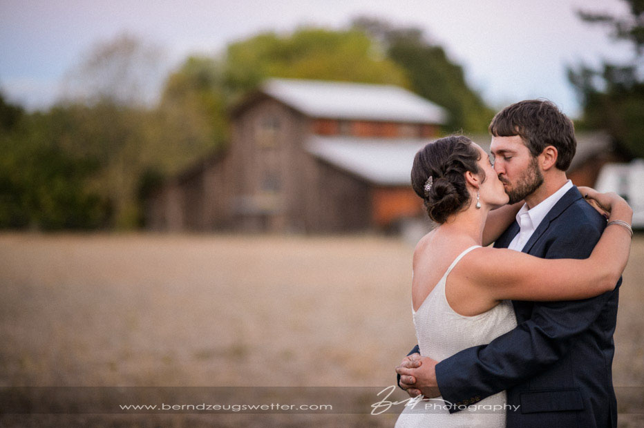 Sonoma wedding photography, couple kissing with barn in background