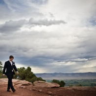 Groom walking in amazing landscape and sky, Colorado National Monument.