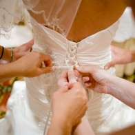 Detail of hands lacing up the wedding gown.