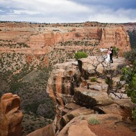 Bride and groom at cliff-side overlooking Wedding Canyon, Colorado National Monument.