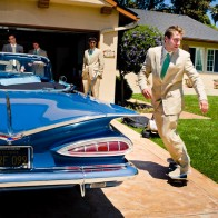 Grooms-man skating out of garage and around vintage car.