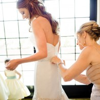 Mother helping bride with the wedding dress at the Montecito Country Club.