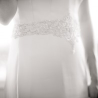 Detail of bride wearing wedding dress.