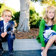 Boy and girl sitting in shade before wedding.