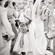 Flower-girl hiding in wedding dress.