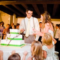 Bride and Groom cutting the cake, kids watching.