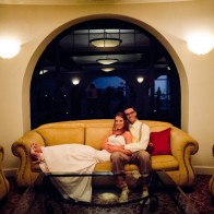 Wedding couple lounging on big sofa at wedding reception, Montecito Wedding Photographer.
