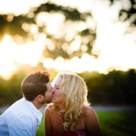 kissing couple on grass with sunset.