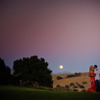 couple hugging in vineyard with full moon.