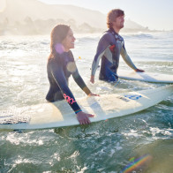 cool shot of couple getting in the water with surfboards.